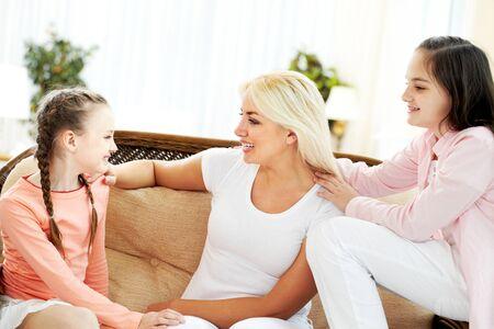 padres hablando con hijos: Retrato de una madre feliz y dos hijas de comunicaci�n en el hogar Foto de archivo