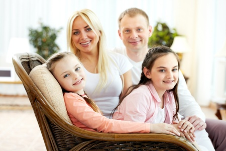 Portrait of happy girls sitting on sofa with their parents on background  photo