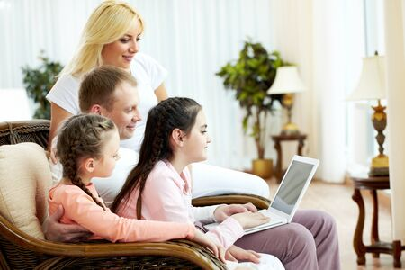 Image of friendly family sitting on the sofa and looking at laptop   photo