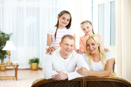 Portrait of happy couple with two children on background looking at camera  photo
