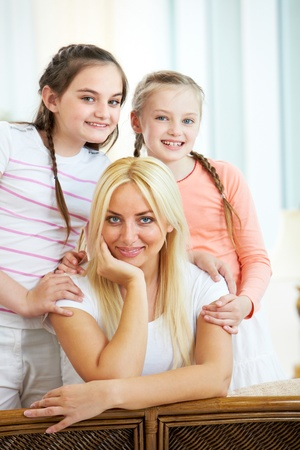 Portrait of happy mother being embraced by two daughters while looking at camera Stock Photo - 9819124