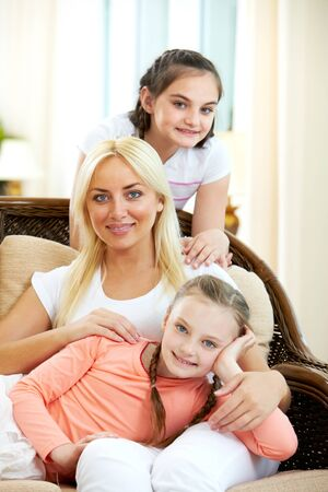 Portrait of happy woman with her daughters sitting on sofa and looking at camera photo