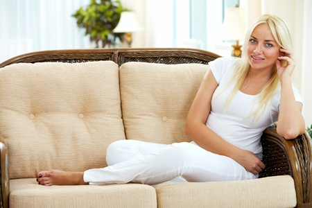 Portrait of charming blonde sitting on sofa and looking at camera photo