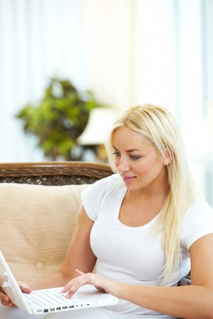 Portrait of charming blonde typing on laptop Stock Photo - 9819350