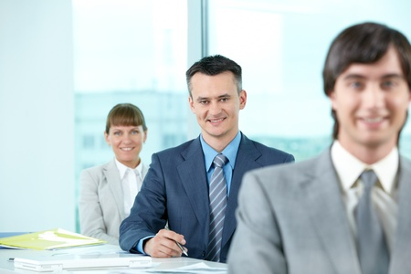 Successful businessman looking at camera between his colleagues Stock Photo - 9819450
