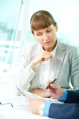 Portrait of confident woman looking at document while her partner explaining it photo