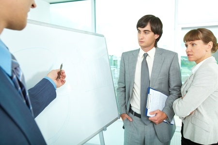 explaining: A group of colleagues looking at whiteboard while their employer explaining them something Stock Photo