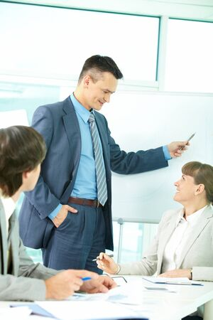 A business man showing something on a whiteboard and looking at colleague photo