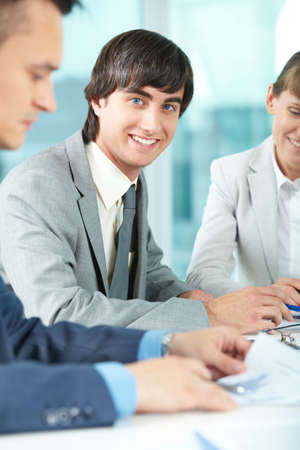 Successful businessman looking at camera between his colleagues Stock Photo - 9819375