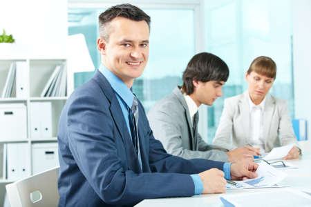 Successful businessman looking at camera in working environment photo