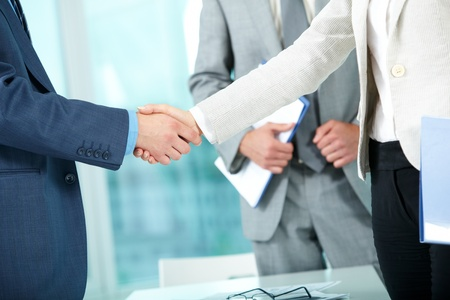 business deal: Photo of handshake of business partners after striking deal on background of man Stock Photo