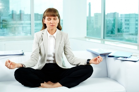 Portrait of attractive office worker meditating in office photo
