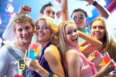 fiestas discoteca: Retrato de chicas alegres con c�cteles en fiesta con amigos felices cerca por