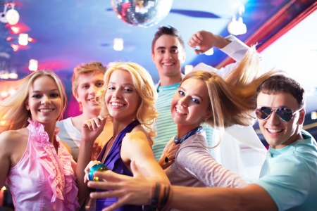 Portrait of glamorous girls dancing at party with happy friends near by photo