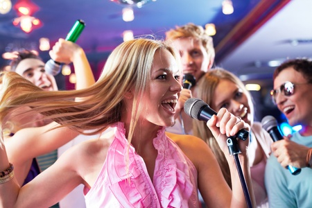 Portrait of joyous girl singing at party on background of happy friends Stock Photo - 9818086