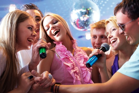 Portrait of joyous guys and girls singing at party together photo