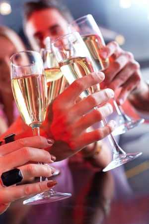 Image of friends hands holding crystal glasses full of champagne photo