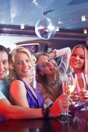 Portrait of boozing people in smart clothing toasting at party photo