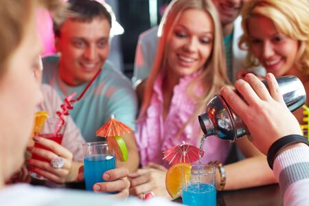 Photo of barman hand holding bottle and pouring water out of it photo