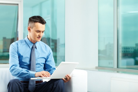 Portrait of pensive man typing in office Stock Photo - 9819439