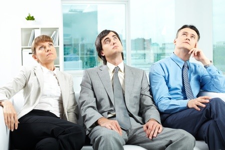 Portrait of pensive employees looking upwards while sitting on sofa in office photo