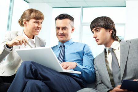 A business team of three sitting in office and planning work photo