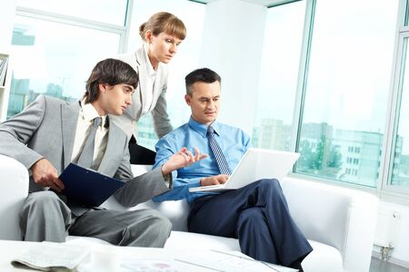 A business team of three sitting in office and planning work Stock Photo - 9819298
