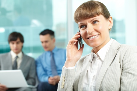 A beautiful businesswoman talking by cellular phone in working environment photo