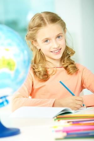 schoolwork: Portrait of smart schoolgirl with blue pencil looking at camera Stock Photo
