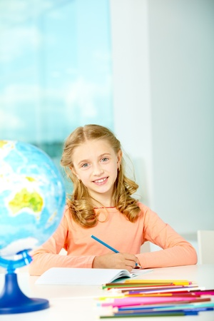 Portrait of smart schoolgirl with blue pencil looking at camera in classroom photo