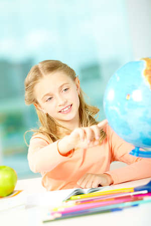 Portrait of cute schoolgirl pointing at globe at workplace photo