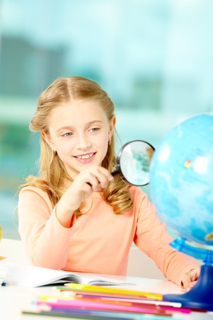 Portrait of cute schoolgirl looking at globe through spy glass photo