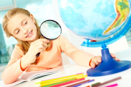 human geography: Portrait of cute schoolgirl looking at globe through spy glass