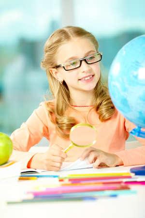 Portrait of cute schoolgirl looking at globe through eyeglasses photo