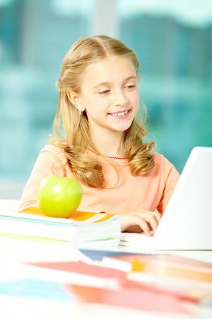 Portrait of smart schoolgirl sitting in classroom and typing photo
