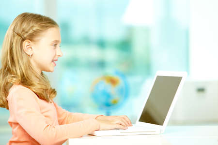 Portrait of smart schoolgirl sitting in classroom and typing photo