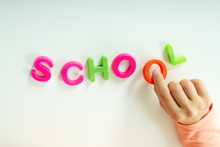 Close-up of girl hand making word �school� from colorful letters photo