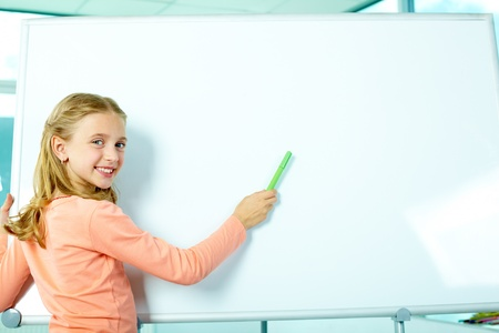 Portrait of smart schoolgirl by the whiteboard looking at camera photo