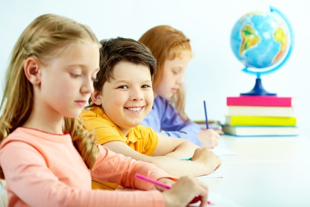 Porträt von smart Schuljunge Blick in die Kamera zwischen Mädchen