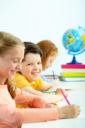 Porträt von glücklich Schuljunge Blick in die Kamera zwischen zwei Mädchen