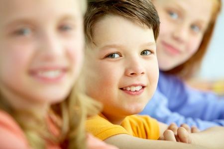 Gesicht des smart Schuljunge Blick in die Kamera zwischen Mädchen Standard-Bild - 9818670