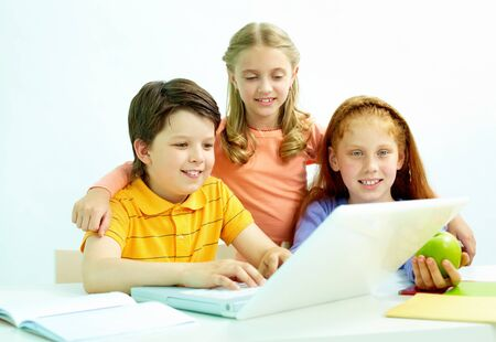 Portrait of smart schoolgirls and schoolboy looking at the laptop in classroom photo