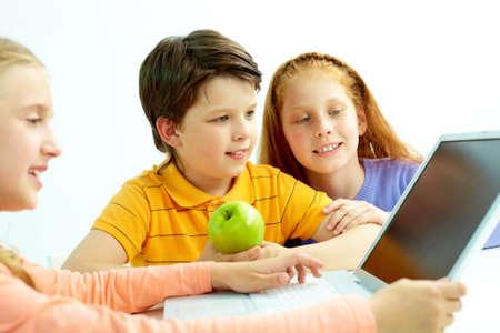 Portrait of smart schoolgirls and schoolboy looking at the laptop screen photo