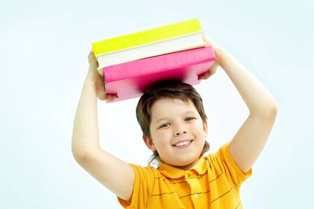 Portrait of smiling lad with stack of books looking at camera photo
