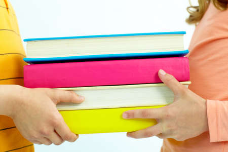 Close-up of childish hand giving books to classmate photo