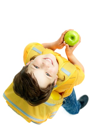 Above view of handsome boy with a green apple isolated on a white background  photo