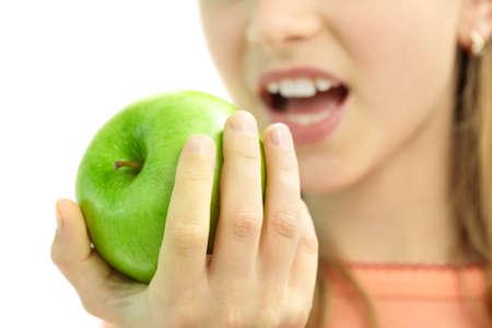 Nahaufnahme des frischen grünen Apfels in der Hand des Schulmädchens, während sie es isst