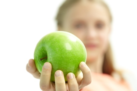 Close-up of fresh green apple in schoolgirl�s hand while she offering it to you photo