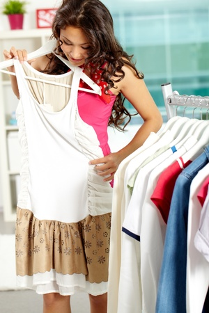 spree: Portrait of pretty woman trying on new dress in clothing department Stock Photo