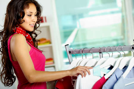 Portrait of happy woman looking through new collection in clothing department photo